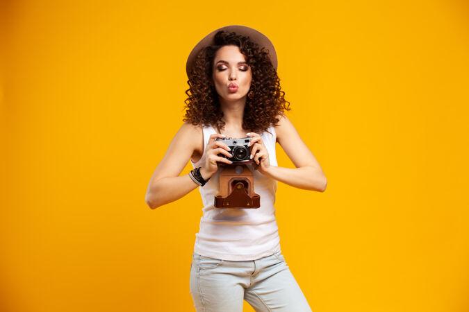在明亮黄色的复古相机上拍摄的笑脸少女肖像