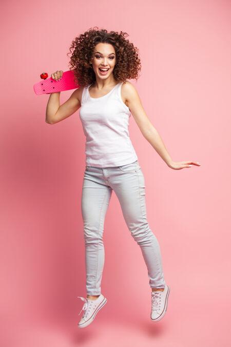 一个穿着夏装的美丽快乐的女人的全长肖像摆姿势 看着远处 一边跳着 一边拿着粉红色的滑板