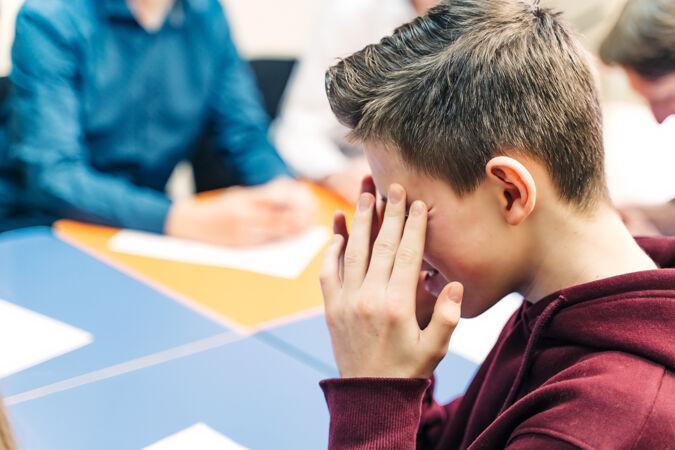 十几岁的男孩低头思考着迷离