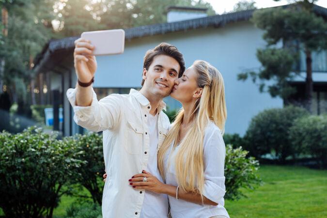 浪漫的照片愉快的快乐的女人亲吻她的男朋友 同时与他自拍