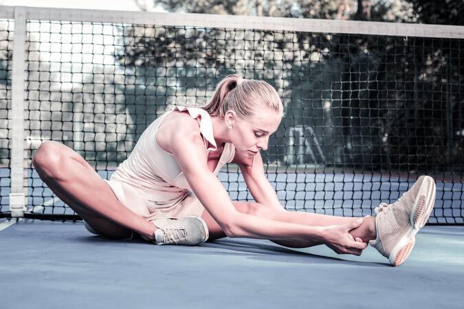 跪下安静的女选手在球场上摆姿势伸展身体