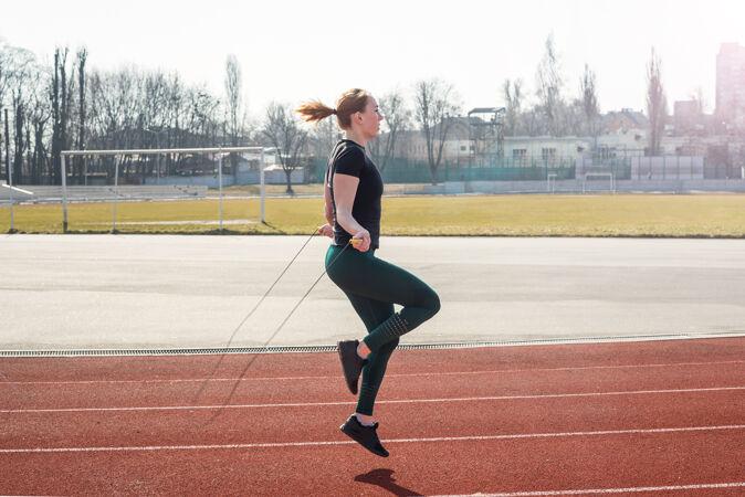 运动 在大自然中锻炼女子在体育场跳绳