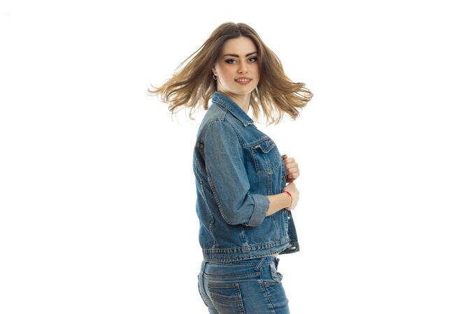 穿着牛仔裤套装的漂亮年轻女子站在一旁 微笑着孤立地站在白墙上