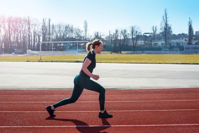 健身和运动运动型女孩在训练前在体育场伸展双腿