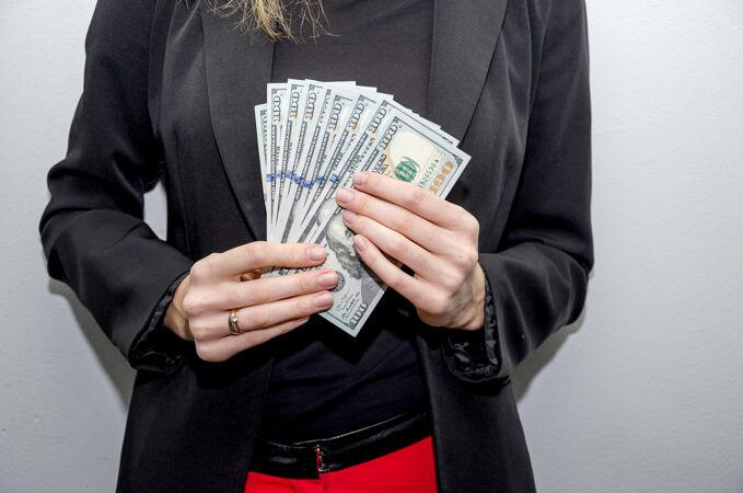 一个手里拿着美元的女商人的特写镜头
