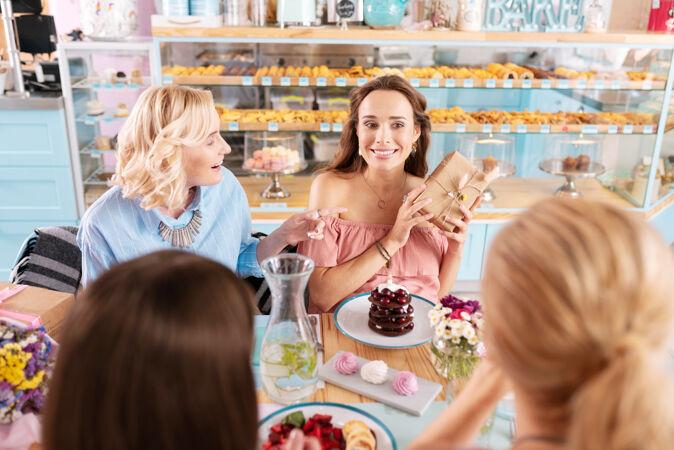 吃甜点四位美丽的成功女性在新面包店边吃甜点边休息