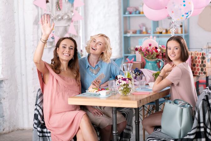 装饰咖啡馆三个女人庆祝婴儿淋浴在漂亮的装饰咖啡馆与许多气球和礼物