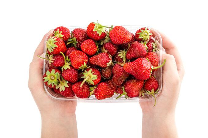 两只手拿着一个白色表面上有草莓的塑料托盘