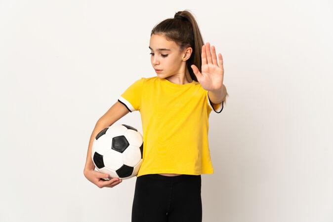 被隔离在白墙上的小足球运动员女人做了一个停车的手势 很失望
