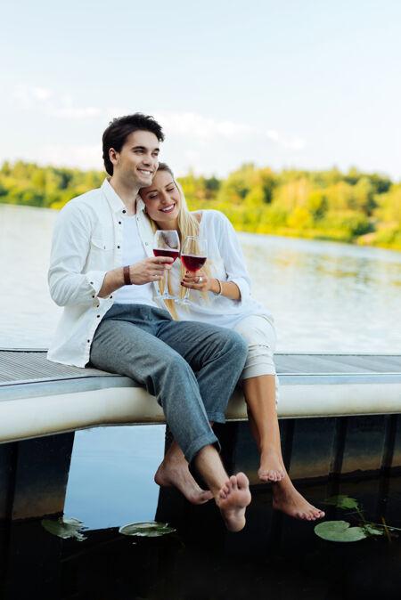 浪漫的野餐快乐的新婚夫妇坐在河边野餐