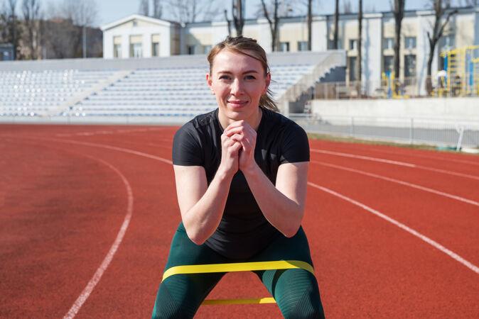 健身和运动概念年轻的运动女性看着摄像机 在红色跑道上用健身松紧带训练她的双腿