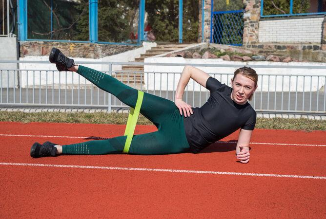 穿着运动服的年轻苗条女子在涂着红色涂料的体育场跑道上用橡皮筋做健身操
