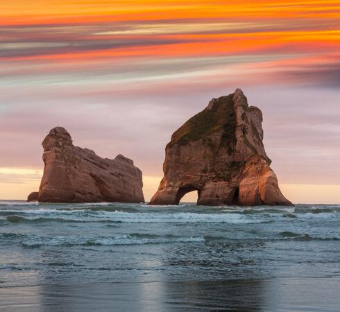 新西兰日落时分的瓦拉里基海滩拱门群岛