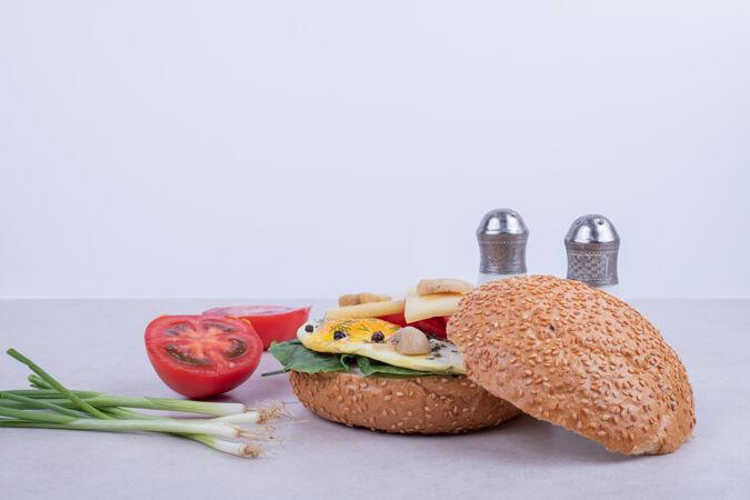 汉堡包 蛋卷 西红柿 蘑菇和洋葱放在白色的表面上