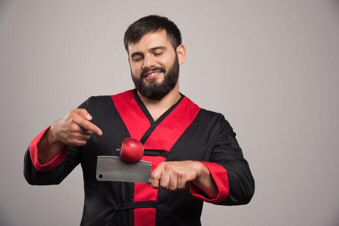有胡子的人指着刀上的红苹果