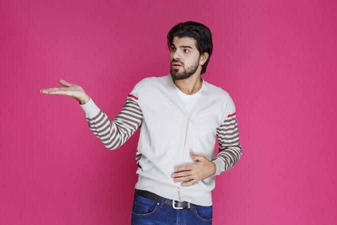 穿白衬衫的人指着某个地方介绍某人或只是指点方向