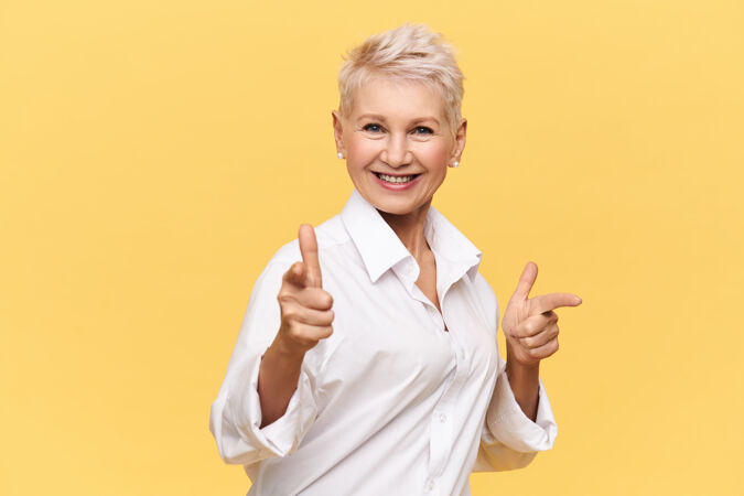快乐迷人的五十岁女性穿着时尚的白衬衫指着前指微笑 选择你与她共舞 面带灿烂的笑容肢体语言