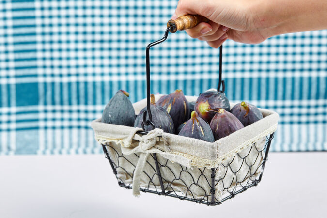 一只手拿着一篮紫色无花果和一块蓝色桌布