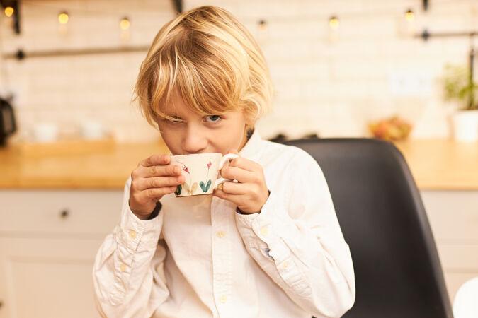 一幅美丽快乐的金发男孩的画像 在放学前一边喝茶一边吃早餐 手里拿着杯子 微笑着拿着厨房柜台上的餐具和花环