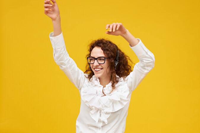 一幅孤立的画面 一头乌黑卷发的积极情绪的年轻女子在黄色的墙壁前摆姿势 双手举在空中 跳舞 戴着耳机听音乐 兴奋地微笑 戴着眼镜